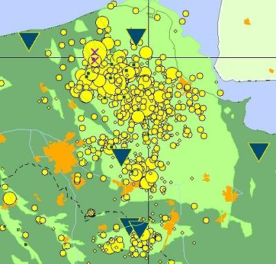 Alle aardbevingen in Groningen van 1990 tot heden (de gele rondjes). De paarse kruisjes: de bevingen van 7 en 8 februari dit jaar. De lichtgroene oppervlakte: het gasveld. De blauwe driehoeken en vierkanten: de meetstations. Afbeelding: KNMI.