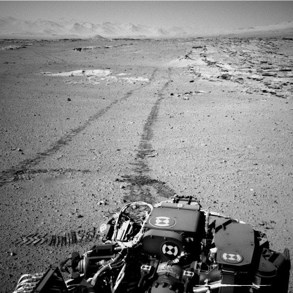 Curiosity gluurt even achterom. Rechts ziet u opnieuw de met stenen bedekte richels. Afbeelding: NASA / JPL-Caltech.