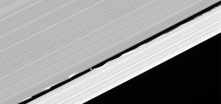Hoewel de ringen heel symmetrisch lijken, is dit niet zo. De manen van Saturnus trekken continu aan de ijs- en stofdeeltjes in de ringen, waardoor er effecten optreden. Op dit kiekje is te zien hoe de kleine maan Daphnis (diameter: 7 kilometer) de A-ring verstoort.