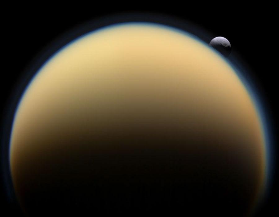 Het maantje Tethys komt op achter Titan. De atmosfeer van Titan is zo dicht, dat het oppervlak niet zichtbaar is.