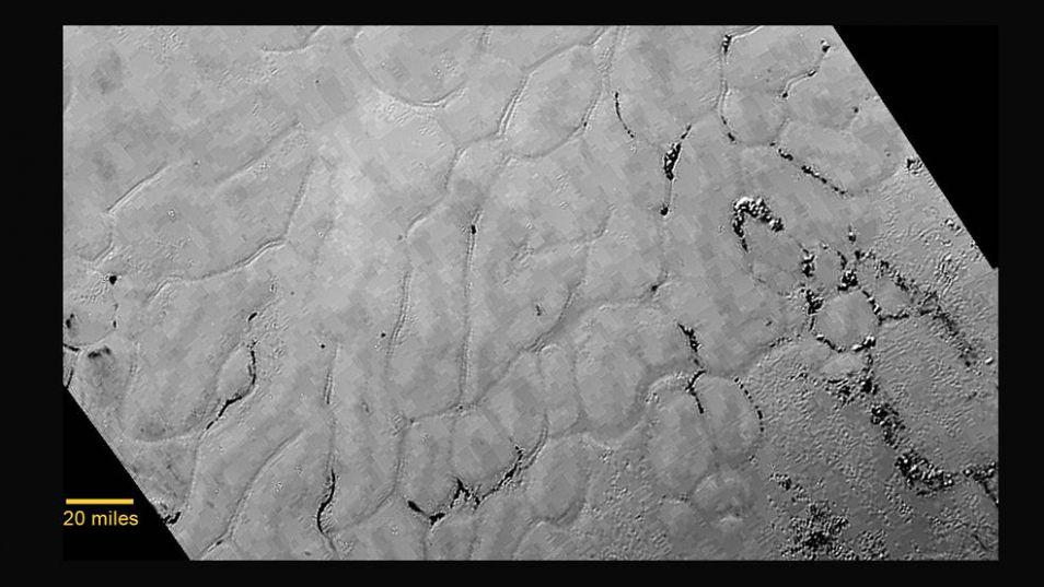 Eén van de meest recente foto's van het oppervlak van Pluto. Op het bevroren oppervlak zijn mysterieuze troggen zichtbaar, die polygone lijnen volgen. Ontstaan deze scheuren in het oppervlak door geologische processen?