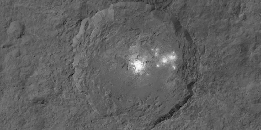 Op deze foto zie je de heldere vlekken in de Occator-krater. Dawn maakte deze foto vanuit de baan waarin de sonde zich de afgelopen twee maanden bevond. De afstand tot Ceres was vanuit die baan ongeveer 1470 kilometer. Afbeelding: NASA / JPL-Caltech / UCLA / MPS / DLR / IDA.