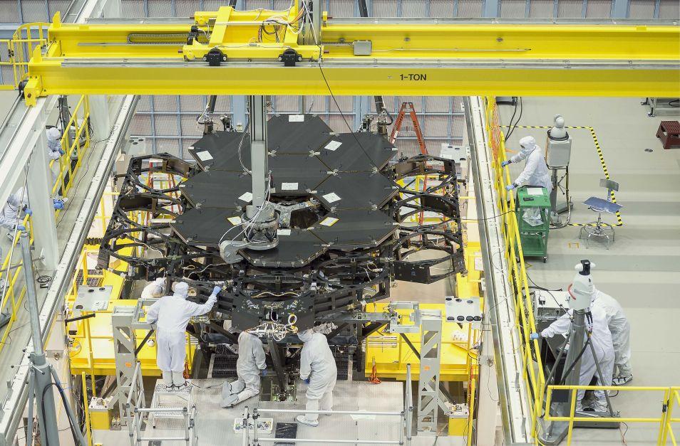 Ingenieurs begeleiden een robotarm, die een spiegel installeert.