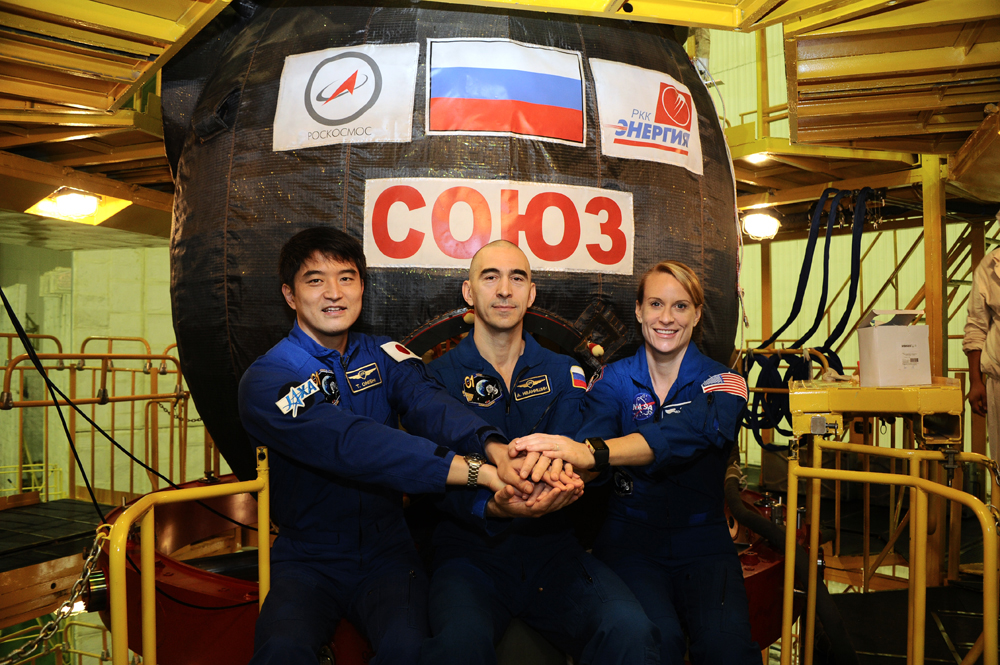 Van links naar rechts: astronaut Takuya Onishi van Japan Aerospace Exploration Agency (JAXA), kosmonaut Anatoly Ivanishin van Roskosmos and NASA-astronaut Kate Rubins poseren in deze foto voor hun Sojoez MS-01 capsule. Foto: RKK Energia.