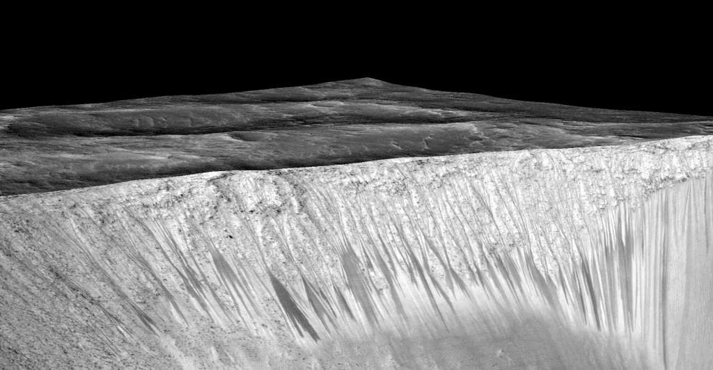 Hier zie je de donkere strepen op een kraterwand. Afbeelding: NASA / JPL-Caltech / Univ. of Arizona.
