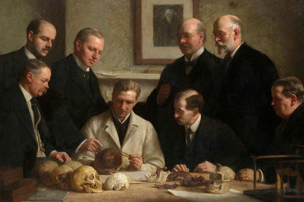 De resten van de Piltdown Man worden bestudeerd. De derde van links (staand) is Charles Dawson. Een schilderij van John Cooke.