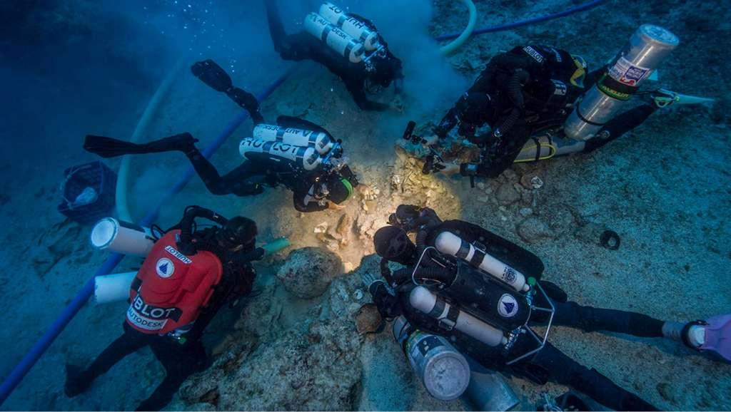 Wetenschappers buigen zich over de resten. Afbeelding: Brett Seymour, EUA / WHOI / ARGO.